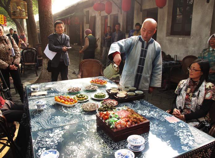 同里的阿婆茶有着悠久的历史,最初是以邻里之间农村老年妇女定期聚会喝茶,谈论家事,了解时事信息而自然形成的生活习俗。同里李记阿婆茶已经有200多年历史,到现任老板李有福这一代,已是第八代传人。   阿婆茶又称吃菜茶、吃讲茶,以前是一种邻里之间农村老年妇女自然形成的生活习俗。一般八人一桌,品茶时的各种佐料,都是各自从家中带来,品种丰富,有茴香豆、熏青豆、阿婆菜、胡萝卜干、瓜子、南瓜饼、青团子,甚至还有话梅等各种蜜饯,拼合在主家的九制盘中,中间的空格由主家放进糖果,意谓甜甜蜜蜜,为了甜住茶客,